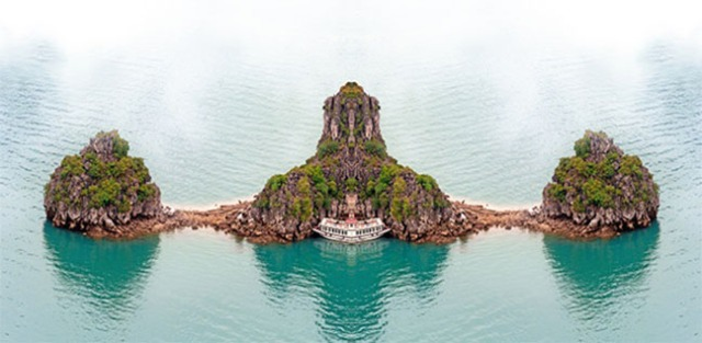 Vietnam Halong Bay cruise boat near tropical island. Aerial phot